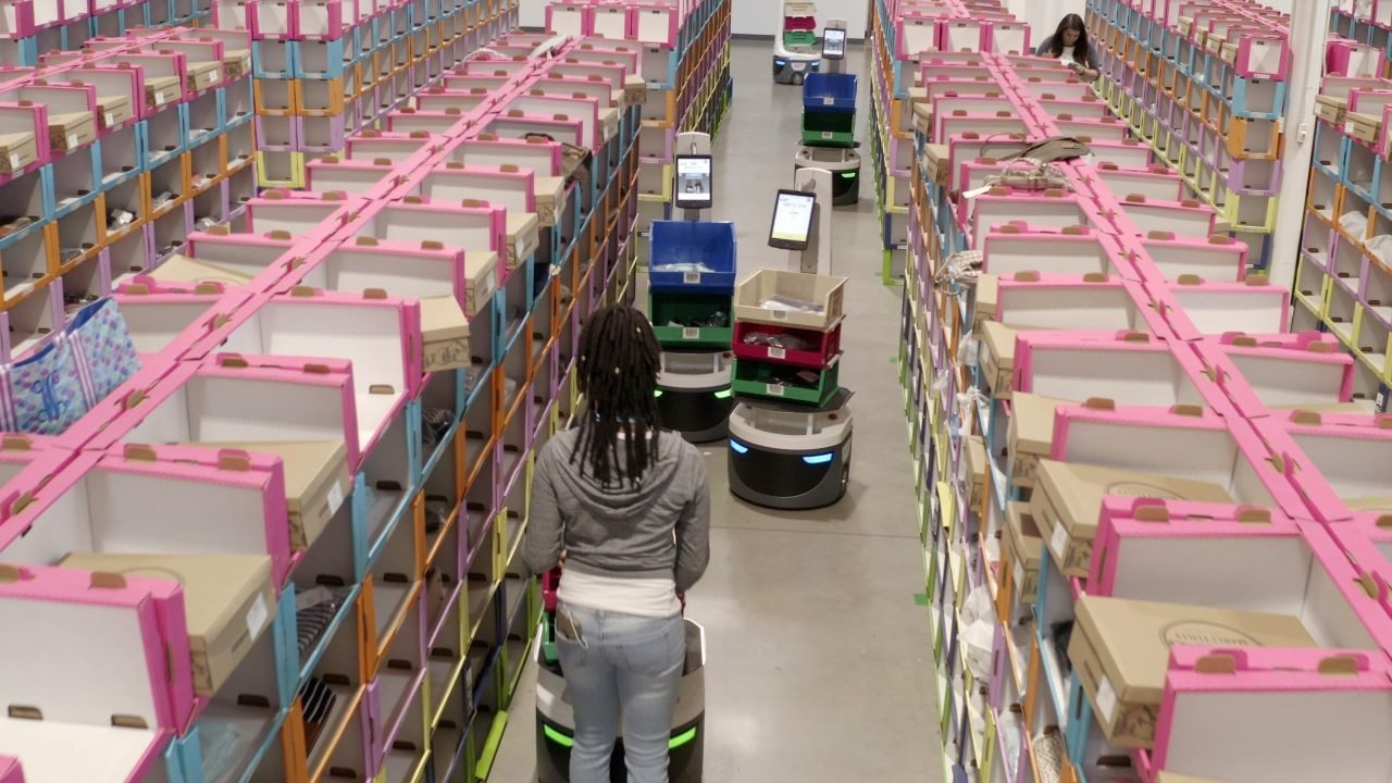 A warehouse worker picks items alongside Locus Robotics` robots.
