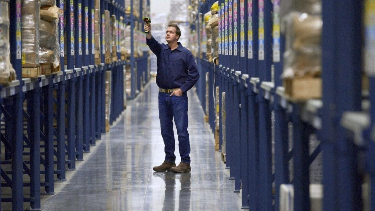 A male warehouse worker uses an extended range barcode scanner to capture information from inventory on high shelves
