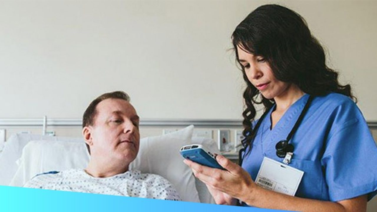 Female healthcare provider uses a handheld touch computer to provide bedside care to a patient