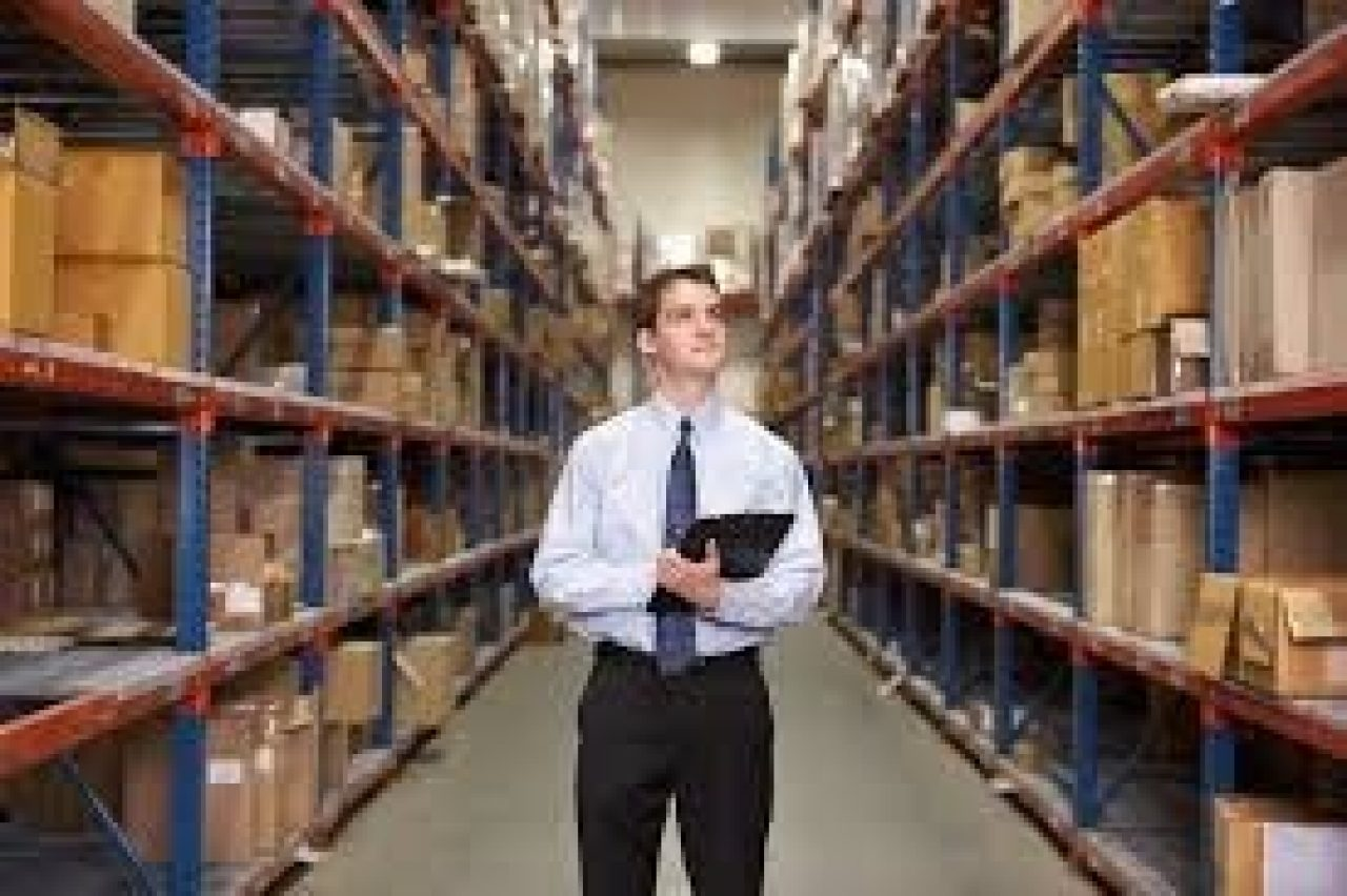 A man stands in the middle of a warehouse aisle with a tablet in hand, looking up at the inventory on the hshelves.