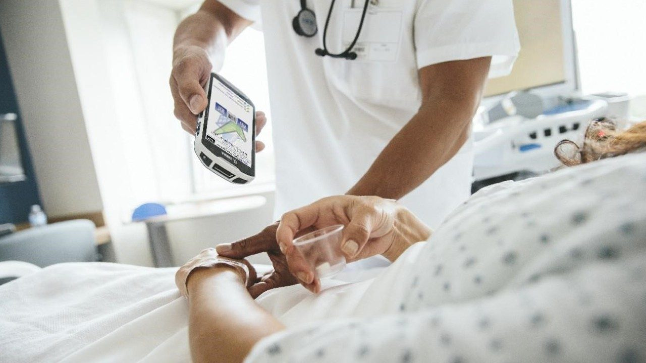 A doctor uses a Zebra handheld mobile computer to scan a patient's barcode\u002Dequipped wristband.