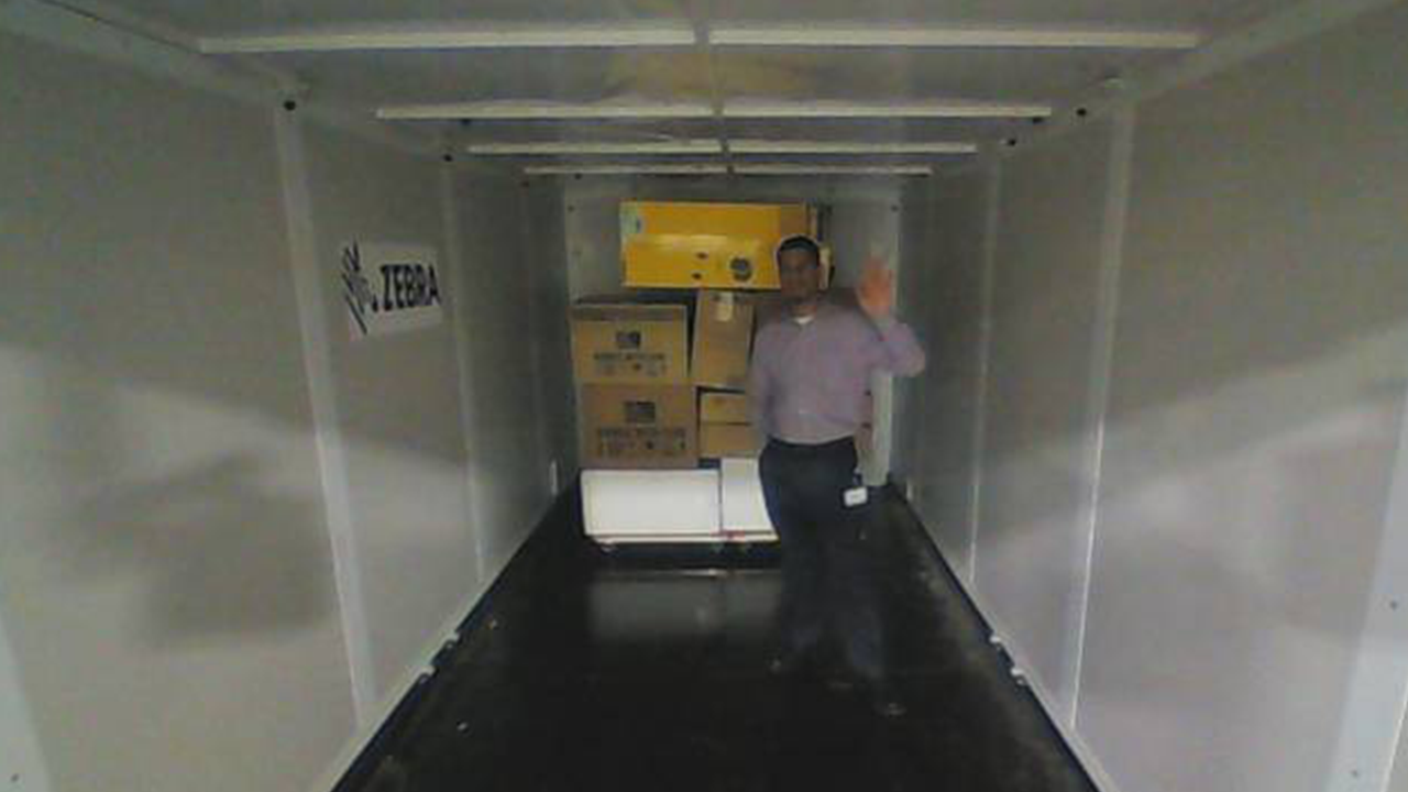 A man stands in a trailer that is practically empty to demonstrate how 3D sensors could help with loading