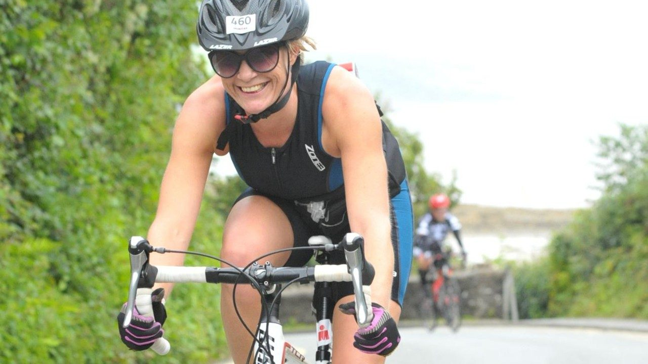 Lorna Hopkin smiles while competing in the biking segment of a recent Ironman race