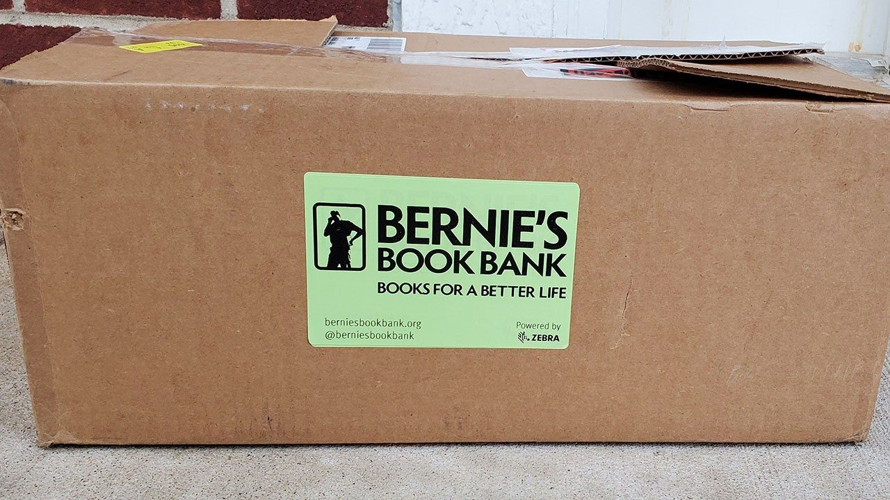 A picture of a Bernie`s Book Bank box with a green label printed with a Zebra printer