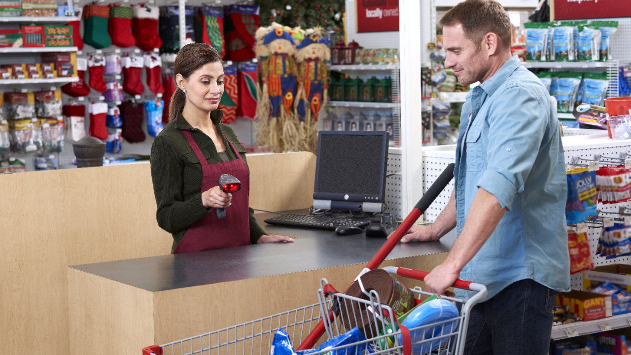 A retail store associate uses a handheld mobile computer to scan items in a customer`s basket from a distance.