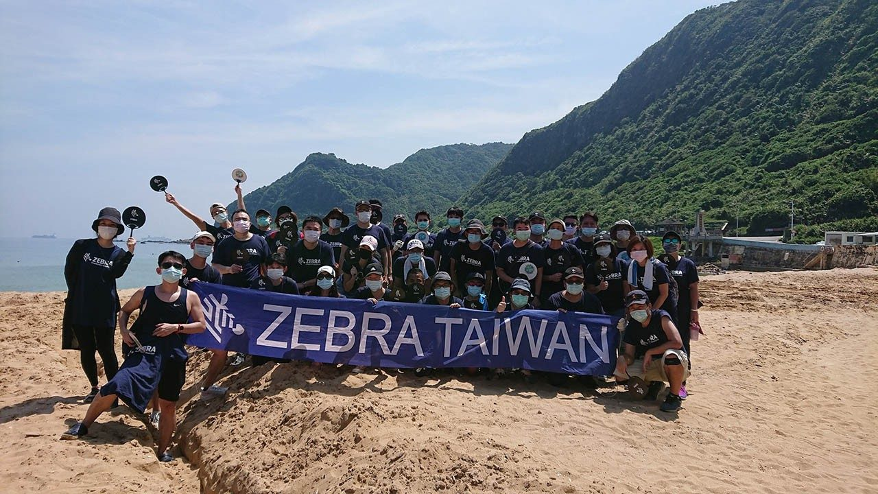 Employees from the Zebra Taiwan office pose for a photo after a recent beach cleanup