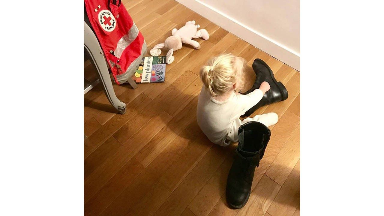 A little girl puts on an adult`s boot while sitting next to a French Red Cross volunteer vest