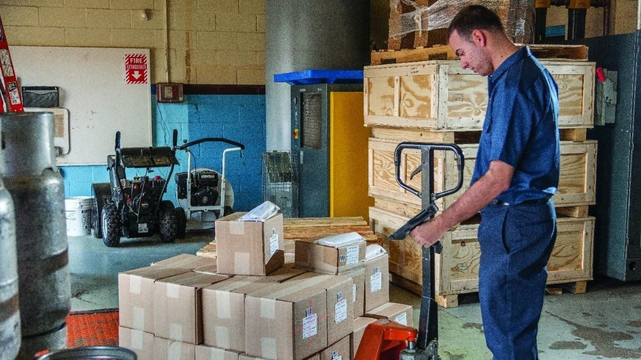 A man uses a mobile computer to scan boxes on a pallet in a warehouse.