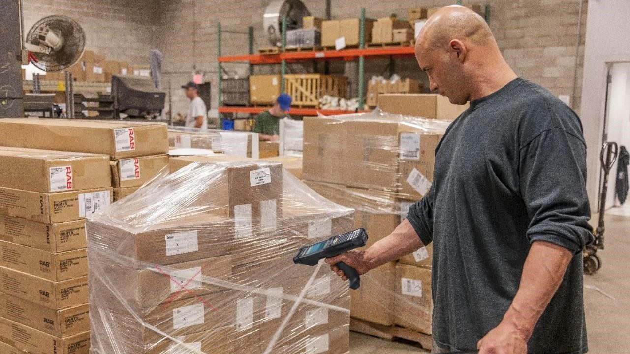 A warehouse worker scans the barcode on a pallet of boxes wrapped in plastic