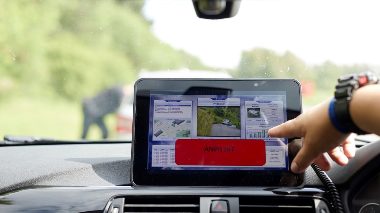 A police officer uses a rugged tablet mounted on the dashboard of the patrol car