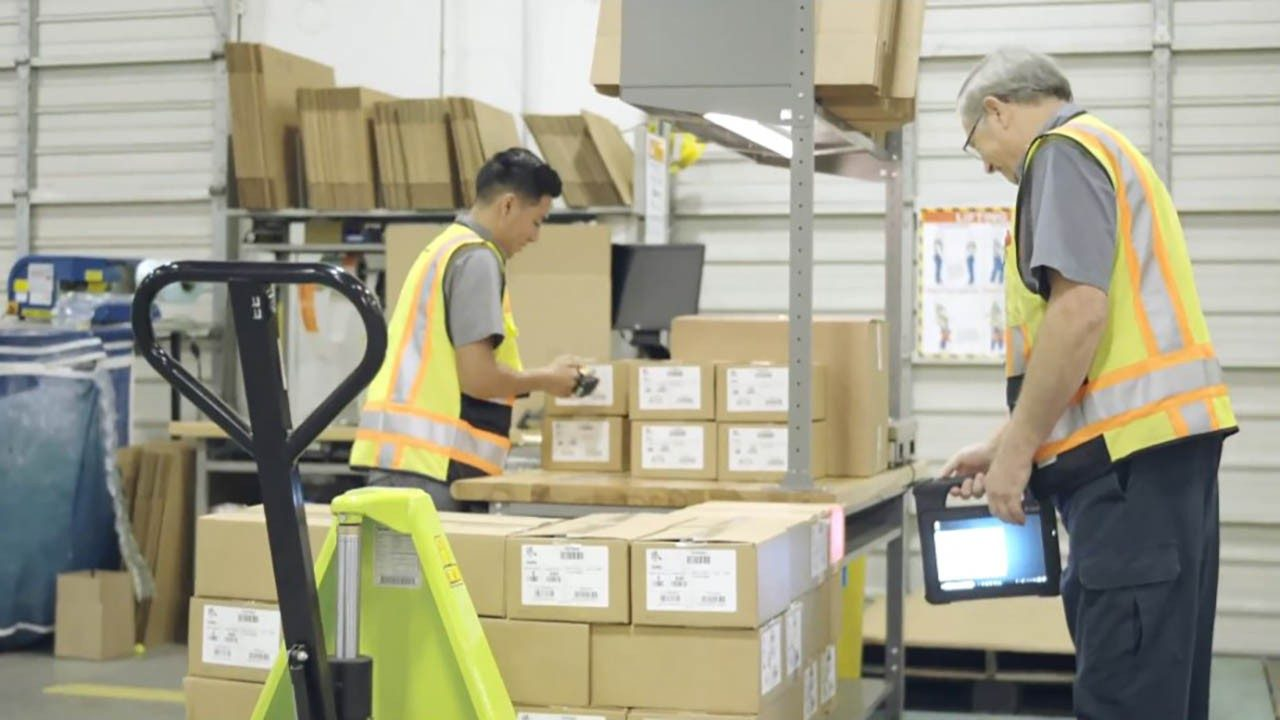 Two Zebra employees use Zebra technology in a warehouse as part of the Zebra4Zebra program