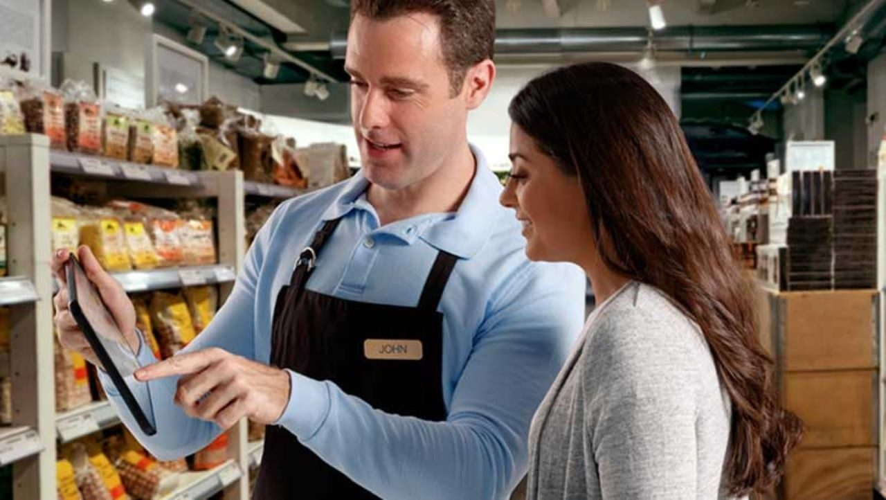 A store associate shows a customer something on a tablet