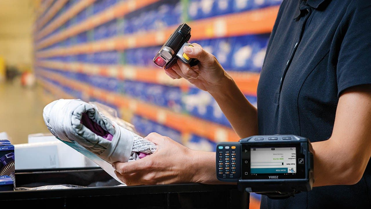 A warehouse worker scans the barcode on an item using a ring scanner connected to a wrist\u002Dworn mobile computer terminal