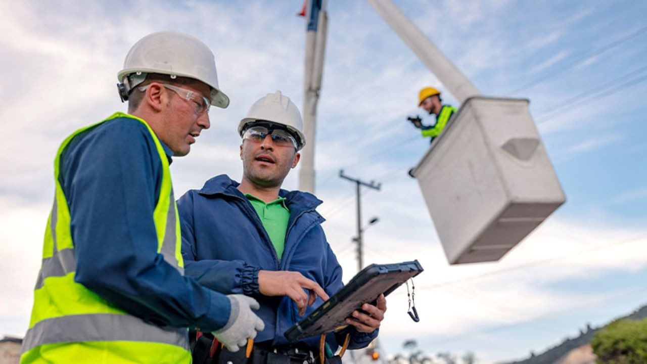 Telco field engineers review information on a Zebra rugged tablet