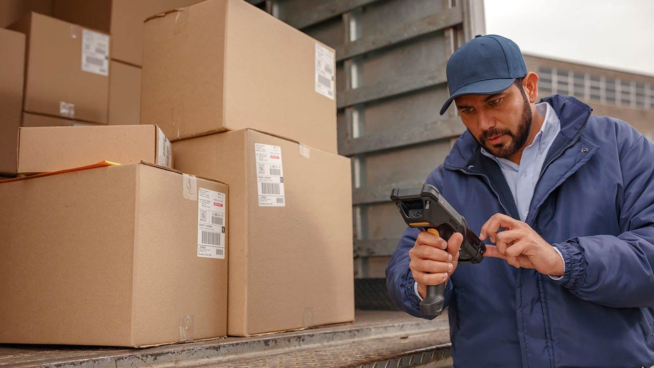 A delivery driver looks at his handheld mobile computer to see which package to deliver nextt