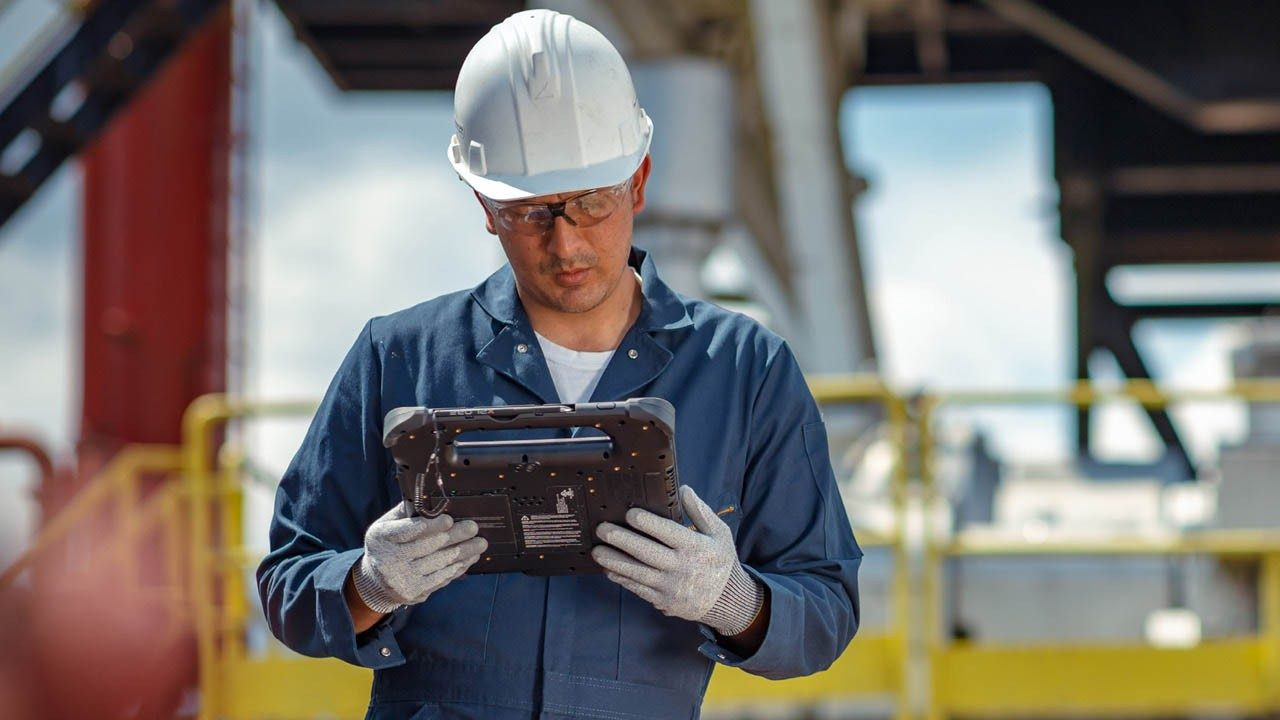An oil and gsa industry worker looks at his rugged tablet screen