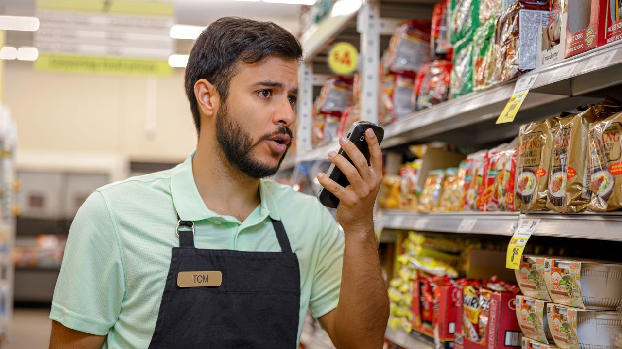 A grocery store associate uses a Zebra TC52 with push\u002Dto\u002Dtalk to communicate with a colleague while looking for an item