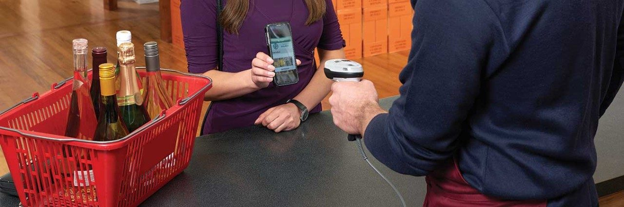 Retail employee uses a barcode scanner to scan retail customer`s mobile device.