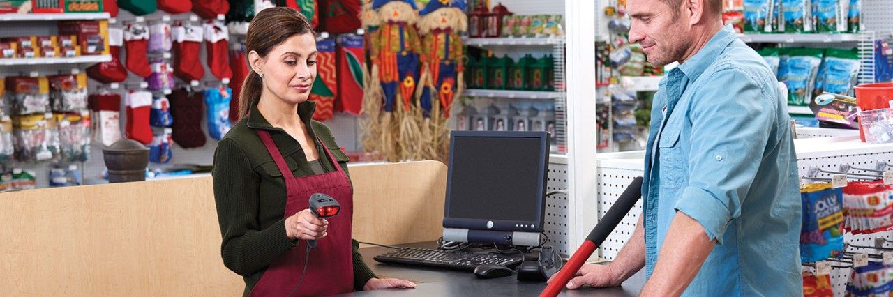 Retail employee using a Zebra DS4608\u002DSR scanner to ring a customer`s items up.