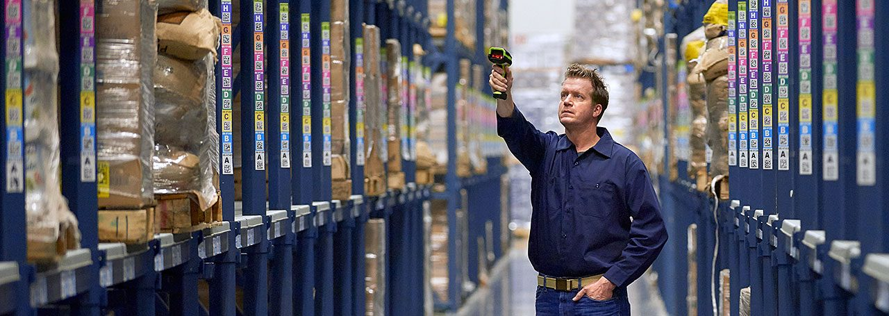 Man in a warehouse scanning inventory with a barcode scanner.