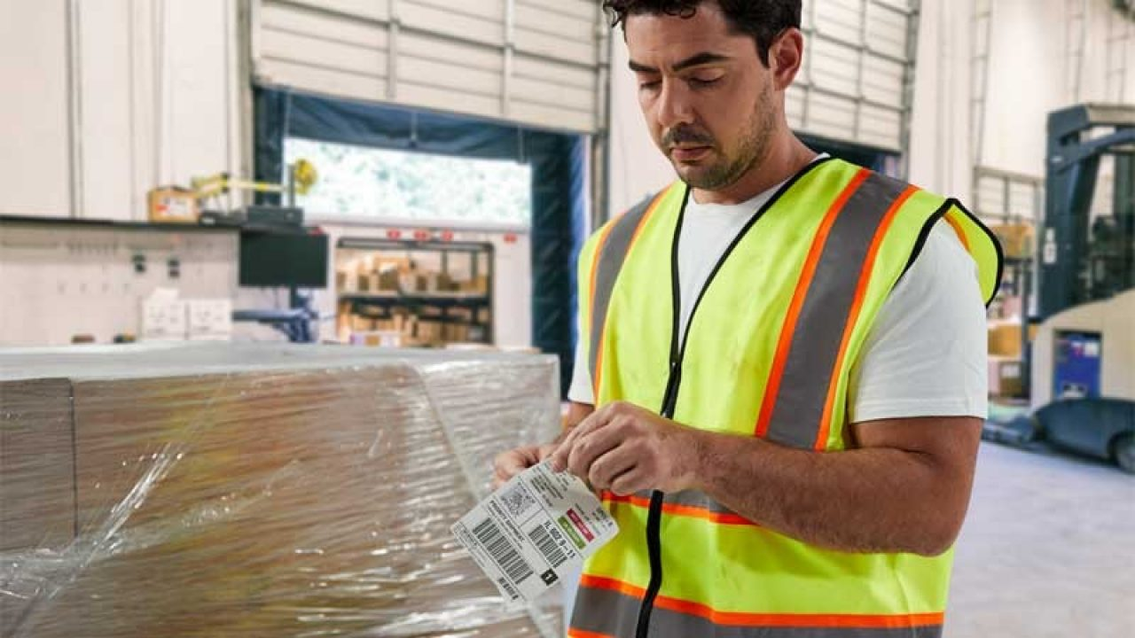 Front view of staff worker using paper labels within the warehouse.