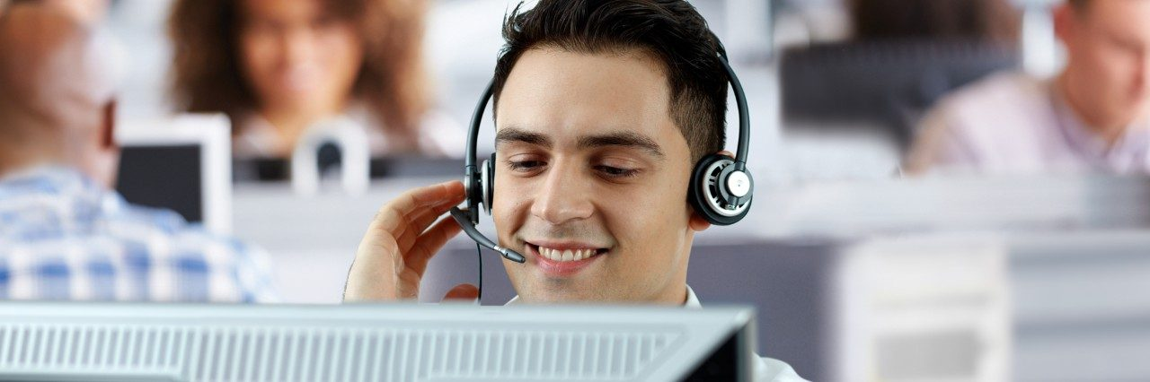 Man speaking into a headset while at his desk