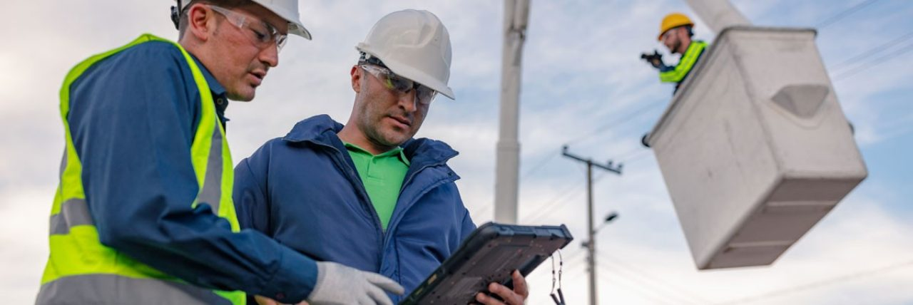 Two workers at an electric site talking over a tablet.