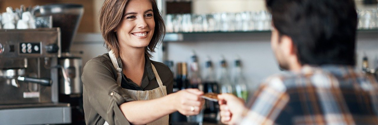 Employee at a coffee shop accepting payment from a customer.
