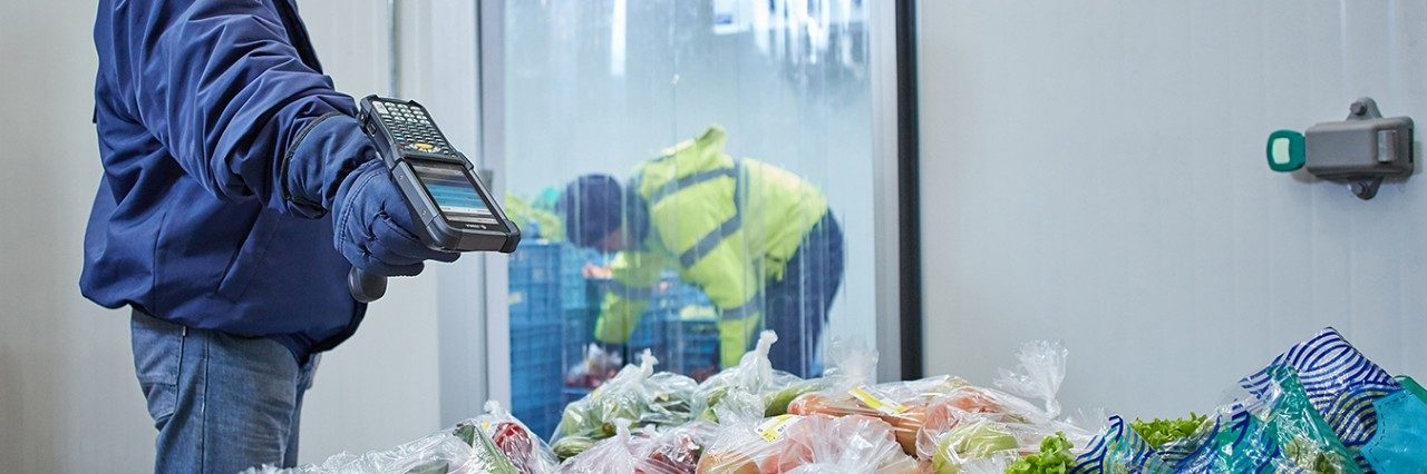 worker scanning boxes of frozen food in cold storage