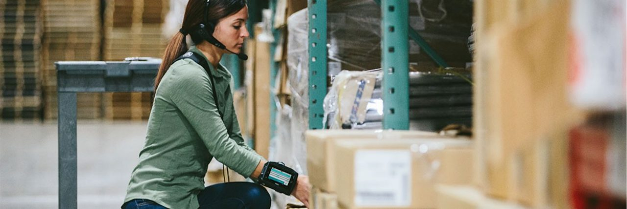 Woman in warehouse using Zebra headset and wearable computer.