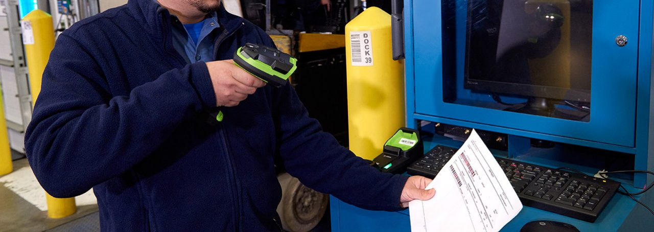 Worker scanning a barcode on a piece of paper using a scanner.