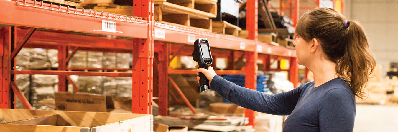 Employee in a warehouse scanning an item using a Zebra device.
