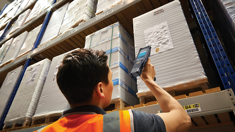 Warehouse employee using a Zebra device to scan a box