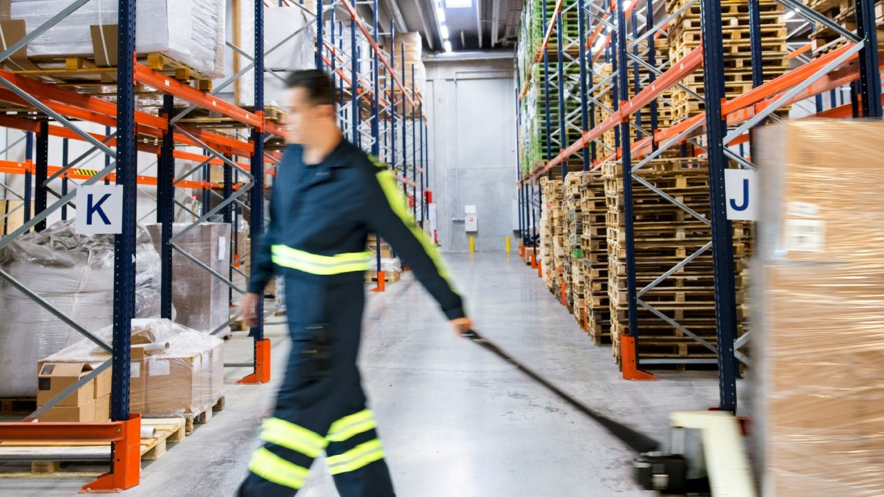 A male worker rolls a pallet through a warehouse.