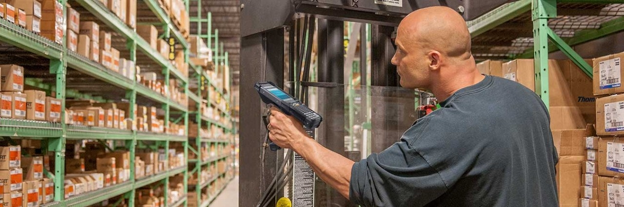Warehouse worker scanning with MC9300 on forklift