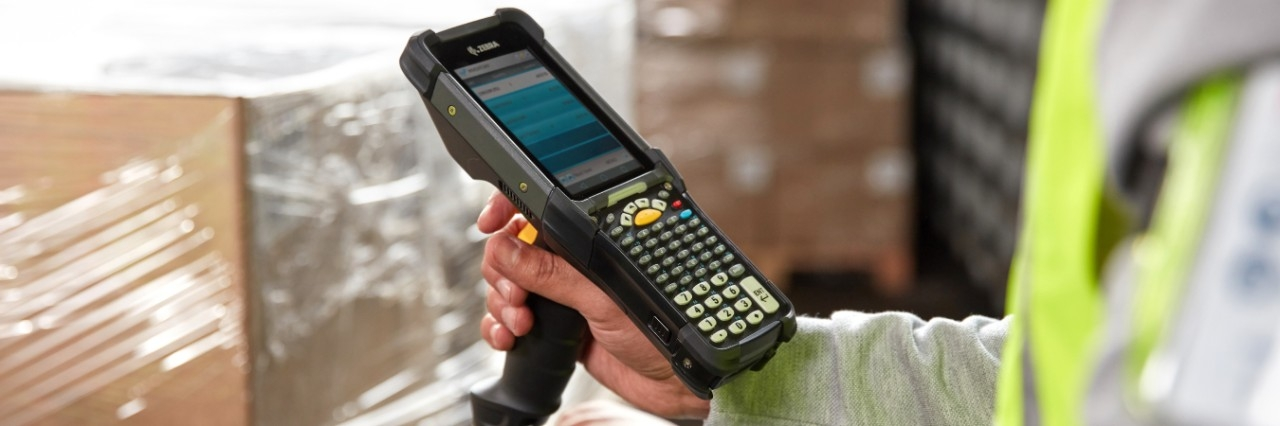 Warehouse worker using a Zebra MC9300 to scan boxes.