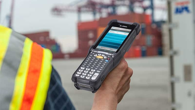 Worker using MC9300 mobile computer at port