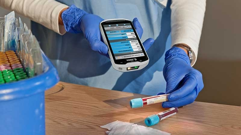healthcare provider scanning a patient vial for specimen labeling