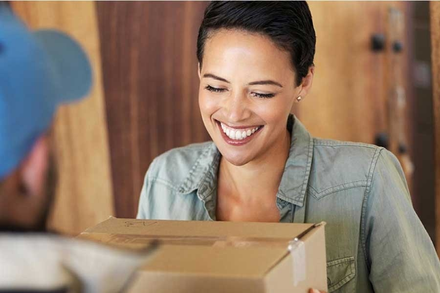 Woman accepting package from delivery person.