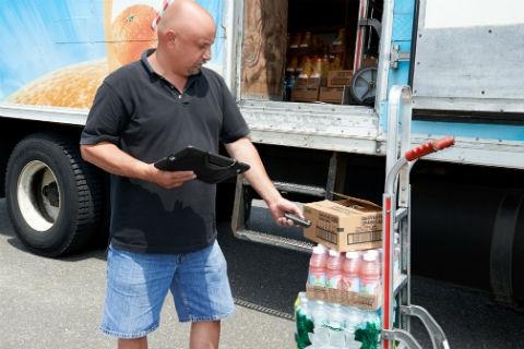 手持平板电脑在扫描包装盒的男士。