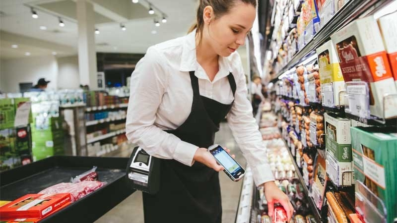 Employee in a grocery store scanning an item using a Zebra device.
