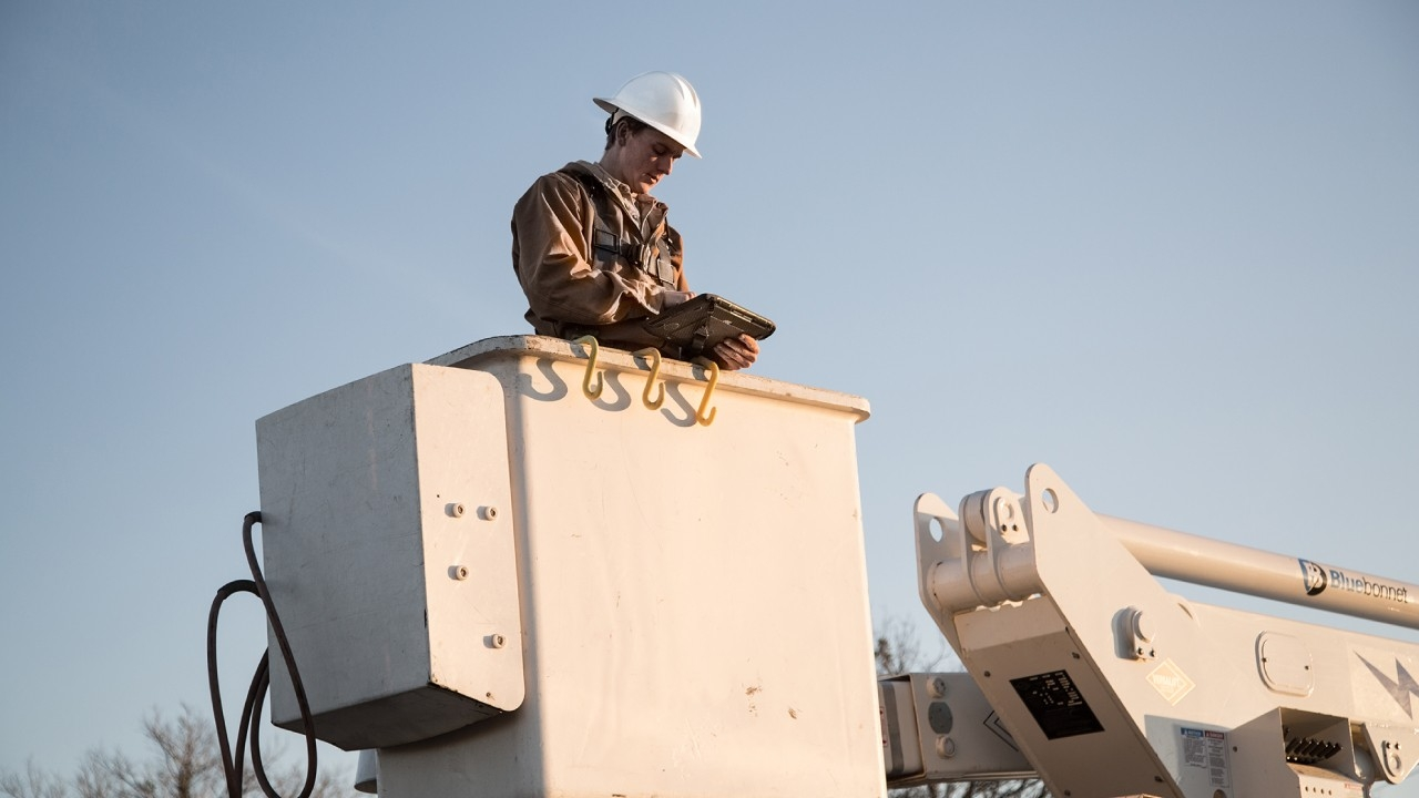 A utility worker looks at a rugged tablet under direct sunlight while standing in a bucket lift.