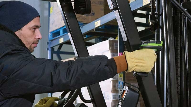 Worker using an ultra\u002Drugged scanner on a forklift in a warehouse