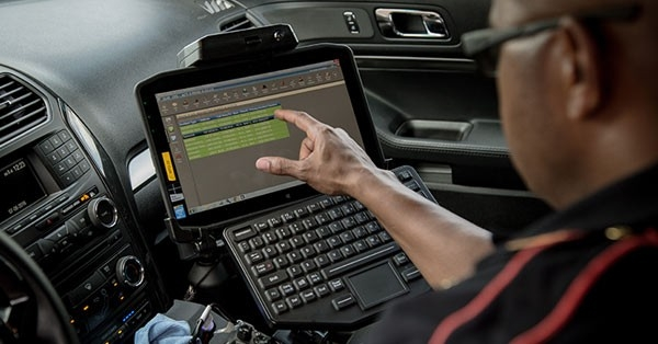 Law enforcement using vehicle\u002Dmounted touch screen 12.5\u002Dinch rugged tablet with full\u002Dsized keyboard to retrieve data.