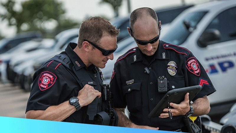 Two police offers using a rugged tablet to maintain real\u002Dtime situational visibility and coordinate with other first responders.