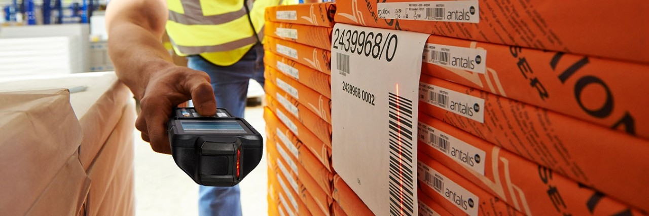 A Zebra MC3300 side scanning a barcode in a warehouse