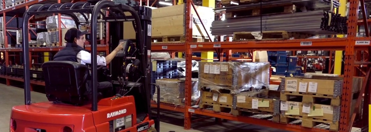 A forklift driver in a warehouse using a Zebra VC80 mounted computer
