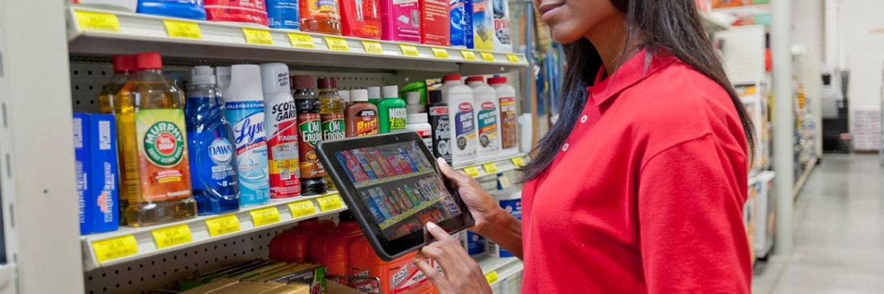 Man holding an ET51\/ET56 tablet and scanning a row of products in a retail environment.