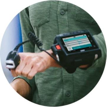 링 스캐너와 착용형 WT6000 컴퓨터로 스캔 작업을 하고 있는 물류창고 직원