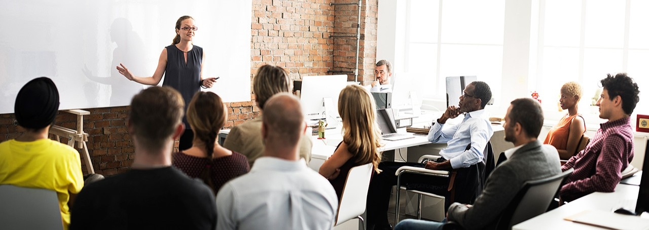 Mujer realizando una presentación frente a un grupo de colegas en una oficina